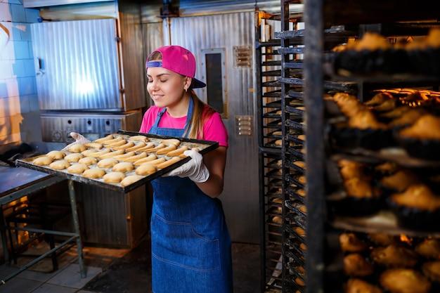 Een professioneel bakkersmeisje houdt een dienblad met verse koekjes in haar handen. zoet gebak in een bakkerij