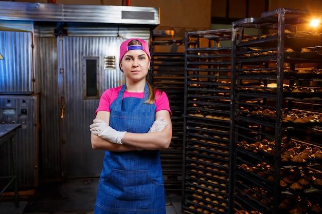 Een professioneel bakkersmeisje staat in de buurt van planken met dienbladen met verse koekjes. zoet gebak in een bakkerij