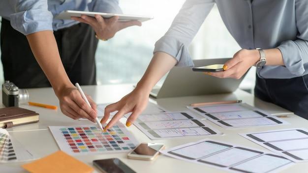 Een professioneel ontwerpteam voor smartphone-applicaties ontwerpt een nieuw project in een modern kantoor.