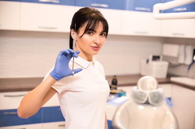Een professioneel portret van een jonge mooie arts-tandarts die een spuit met verdovingsmiddel in haar tandartsbureau houdt