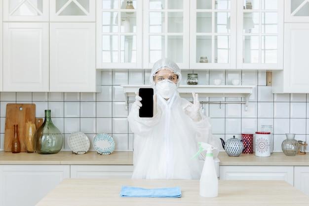 Een professionele aannemer van ongedierte of virussen staat in de keuken en toont een positief teken. het concept van een pandemische coronavirus-desinfectie of covid-19