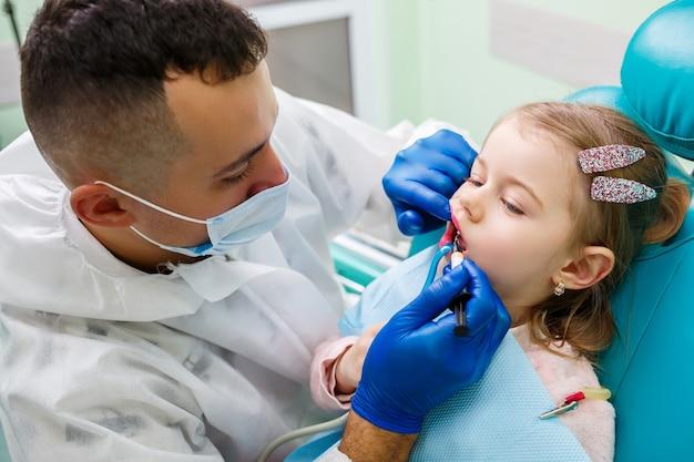 Een professionele arts, een kindertandarts, behandelt de tanden van een klein meisje met instrumenten. tandartspraktijk voor patiëntonderzoek. het proces van tandheelkundige behandeling bij een kind
