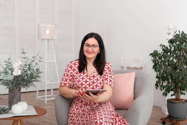 Een professionele arts-psycholoog met bril zit in een helder kantoor met een tablet