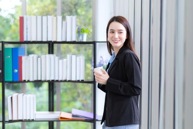 Een professionele aziatische zakenvrouw kijkt uit het raam waarin ze een koffiekopje vasthoudt.