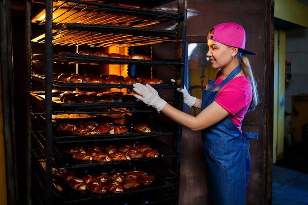 Een professionele bakker staat bij het rek met verse broodjes. zoet gebak bij de bakker