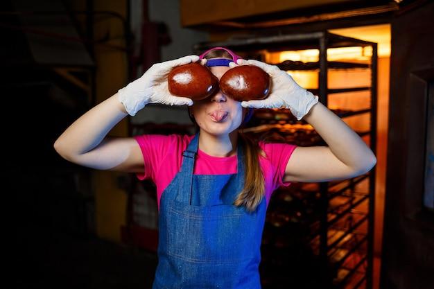 Een professionele bakkersvrouw houdt verse broodjes in haar handen en hoort hun geur in de bakkerij. ze draagt een spijkerbroek en een pet. productie van bakkerijproducten. rek met warme knapperige gebakjes.