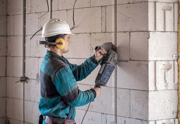 Een professionele bouwer in werkkleding werkt met een snijgereedschap.