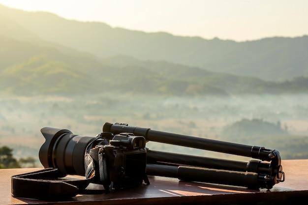 Een professionele dslr camera en statief in de natuur