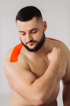 Een professionele fysiotherapeut die rekbare kinesiologietape op de arm en schouder van de patiënt plakt.
