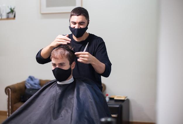 Een professionele kapper die een beschermend masker draagt dat het haar naar een klant knipt tijdens het coronavirus Premium Foto
