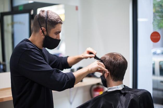 Een professionele kapper die een beschermend masker draagt dat het haar naar een klant knipt tijdens het coronavirus