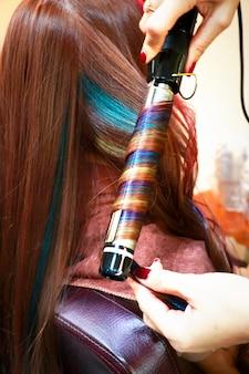 Een professionele kapper strijkt veelkleurig haar en ziet eruit als een spiraalvormige regenboog