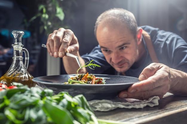 Een professionele kok versiert een maaltijd net voordat hij deze aan een klant serveert in een restaurant, pub of hotel.
