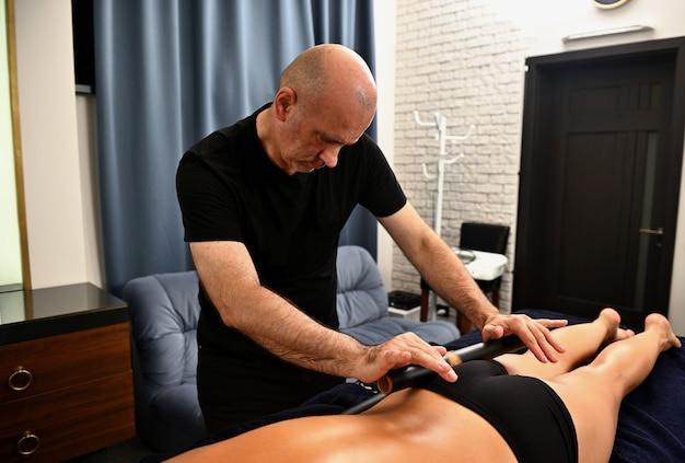 Een professionele masseur maakt een lichaamsmassage voor een jonge vrouw met behulp van een bamboestok. ayurvedische lichaamsverzorging in de spa