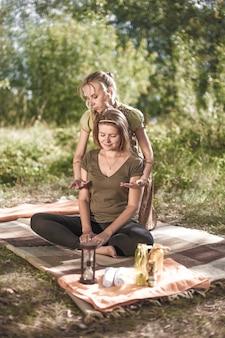 Een professionele masseuse voert een ontspannende massage uit in de natuur.