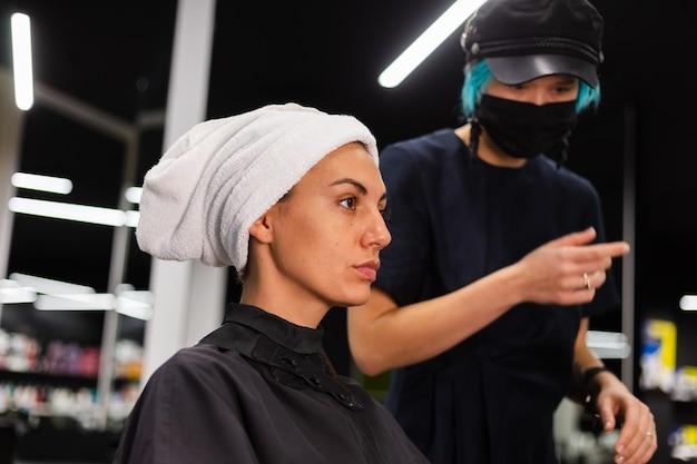 Een professionele meisjeskapper maakt het kapsel van een cliënt. het meisje zit in een masker in de schoonheidssalon Gratis Foto