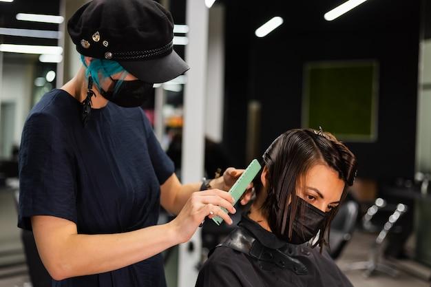 Een professionele meisjeskapper maakt het kapsel van een cliënt. het meisje zit in een masker in de schoonheidssalon