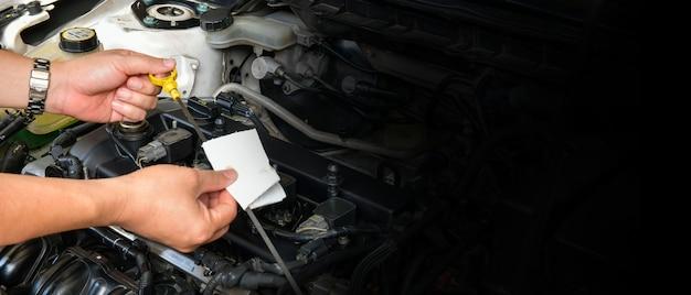 Een professionele monteur houdt de oliepeilstok vast, controleer het oliepeil in de automotor, kopieer ruimte