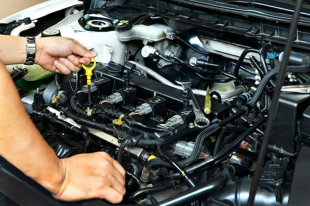Een professionele monteur houdt de oliepeilstok vast en controleert het oliepeil in de automotor