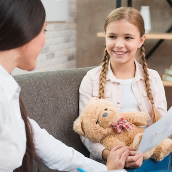 Een professionele psycholoog die een vergadering met een meisje heeft dat op bank zit