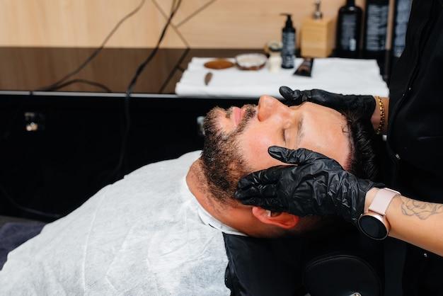Een professionele stylist in een moderne, stijlvolle kapperszaak scheert en knipt het haar van een jonge man. schoonheidssalon, kapsalon.
