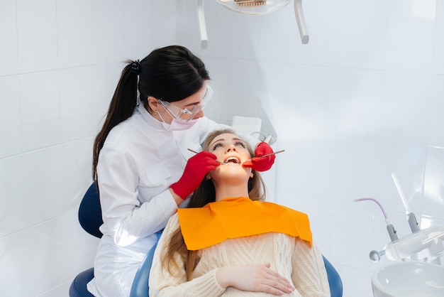 Een professionele tandarts behandelt en onderzoekt de mondholte van een zwangere vrouw in een moderne tandartspraktijk. tandheelkunde