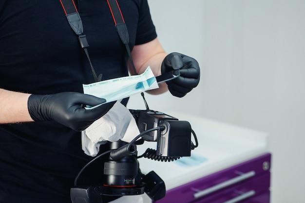 Een professionele tandarts haalt een gedesinfecteerde spiegel uit de verpakking om occlusale foto's van het gebit van de patiënt te maken.