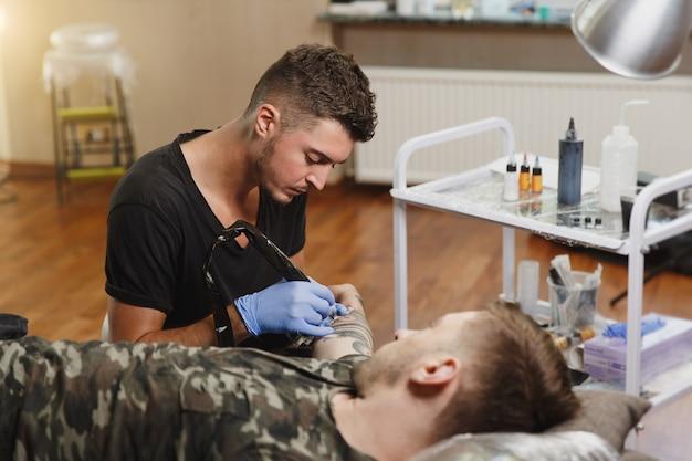Een professionele tatoeëerder die tatoeage op de arm van een jonge man doet door een machine met zwarte inkt