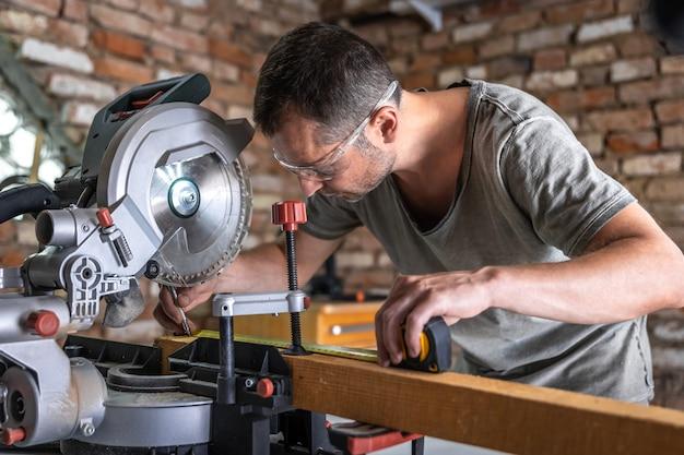 Een professionele timmerman werkt met een cirkelzaag-verstekzaag in een werkplaats.