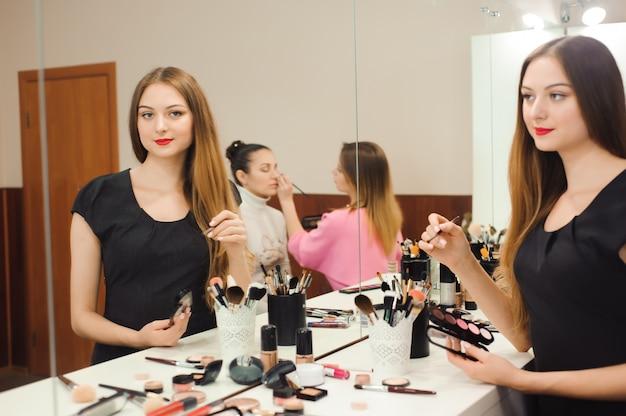 Een professionele visagist bereidt zich voor om voor een spiegel te werken.