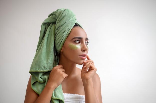 Een profielfoto ontspannen vrouw, heeft een frisse, gezonde huid, draagt collageenpleisters onder haar ogen