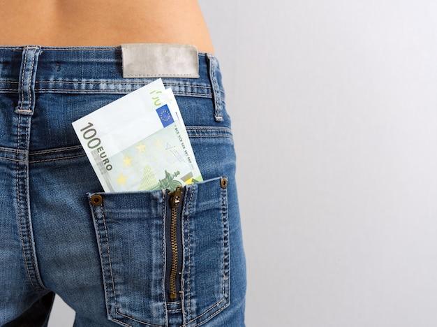 Een prop biljetten van honderd euro steekt uit de achterzak van een damesjeans. horizontale foto. geld in je zak, kopieer ruimte