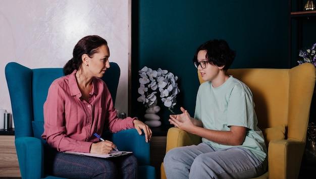 Een psycholoog en een tienerpatiënt zitten in een stoel en hebben een gesprek