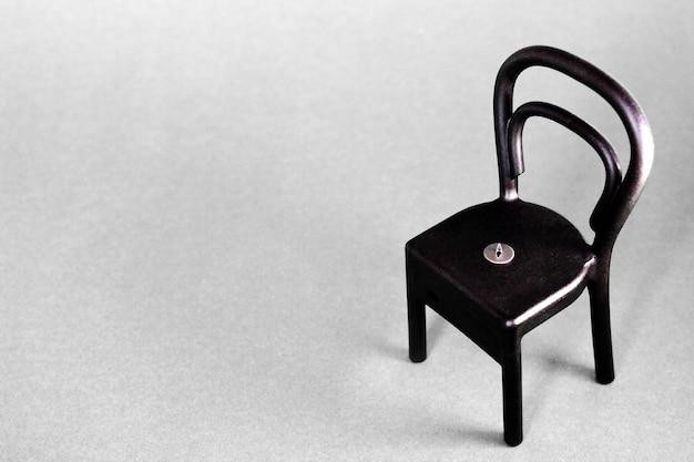 Een punaise op de zwarte plastic stoel op grijs