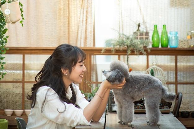 Een puppy en een dame spelen op een zonnig huiskamerbed