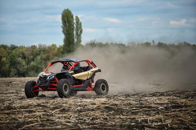 Een quad racet langs een schuin veld