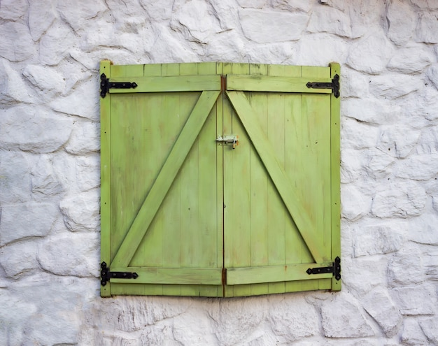 Een raam gemaakt van hout en groene kleur op een muur met witte cementstructuren