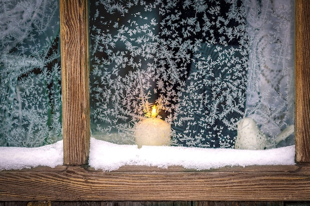 Een raam met houten kozijnen, ijzige patronen. buiten het raam brandt een kaars.