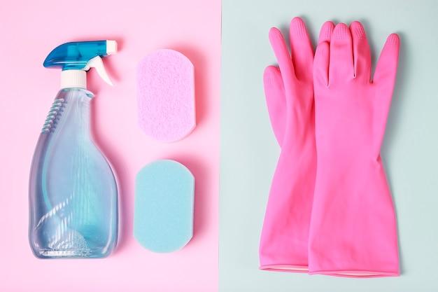 Een raamspray, spons op blauwe en roze achtergrond bovenaanzicht, voorjaarsschoonmaak concept