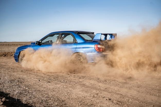 Een rallysportwagen die op de drit-grindrace rijdt, hoge snelheid met modderspatten