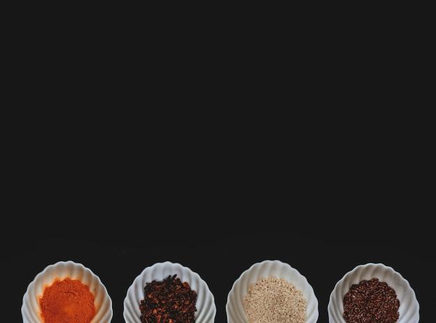 Een rand van specerijen en granen in witte kopjes op een zwarte geïsoleerde achtergrond. bovenaanzicht