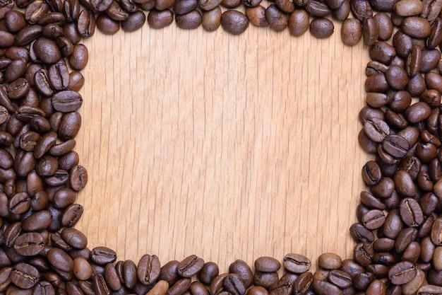 Een rechthoekige leegte is aangelegd op een houten oppervlak gemaakt van koffiebonen. er is ruimte in de leegte
