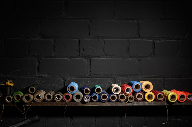 Een reeks draden van verschillende kleuren ligt op een houten plank