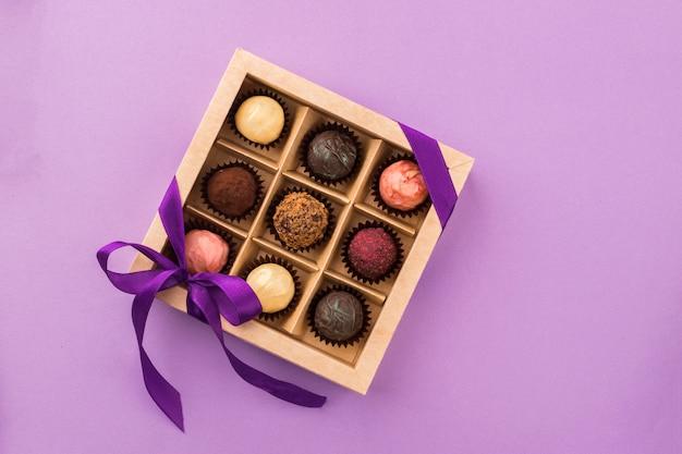 Een reeks geassorteerde chocolaatjes in een papieren doos met een satijnen paars lint
