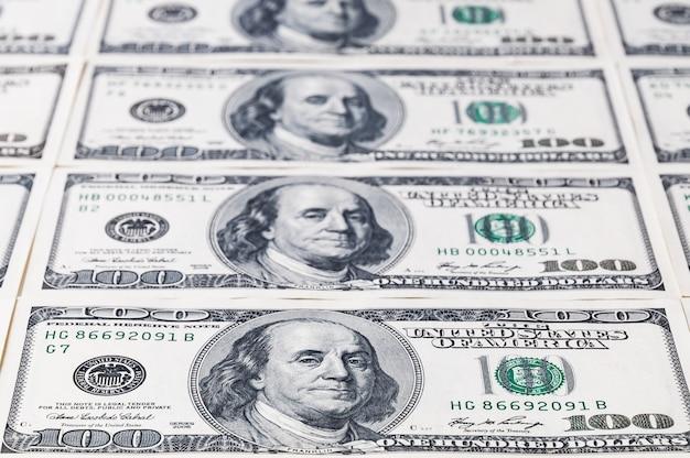Een reeks honderd-dollar bankbiljetten die in de afstand weggaan. focus op het eerste bankbiljet.