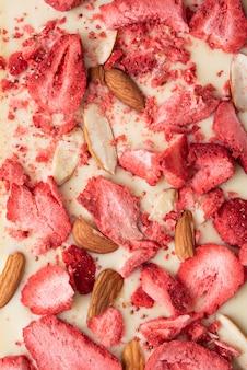 Een reep witte chocolade met gebakken amandelen en gevriesdroogde aardbeien op een lichte achtergrond, voedsel achtergrond.