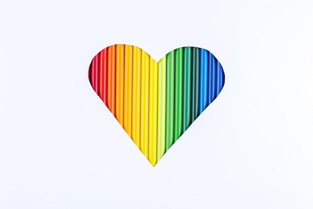 Een regenboog van potloden in een uitgesneden hart op een witboekachtergrond.