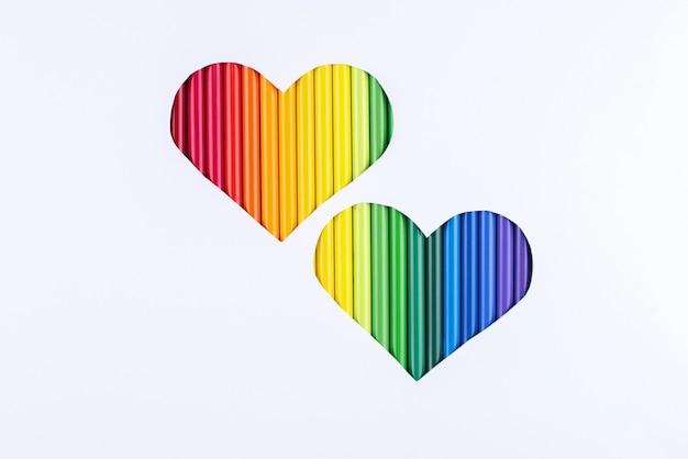 Een regenboog van potloden in twee uitgesneden harten op een wit papier achtergrond.