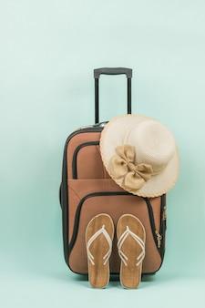 Een reiskoffer, een dameshoed en damessandalen op een blauwe achtergrond. het concept van zomerreizen.