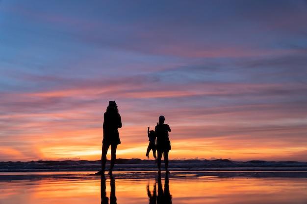 Een reismeisje dat bij wit zandstrand tijdens zonsondergangtijd ontspant